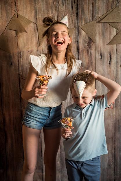 女の子、男の子の木製のテーブル背景にボウルに食べるポップコーンを共有します。共有のコンセプトです。 Premium写真