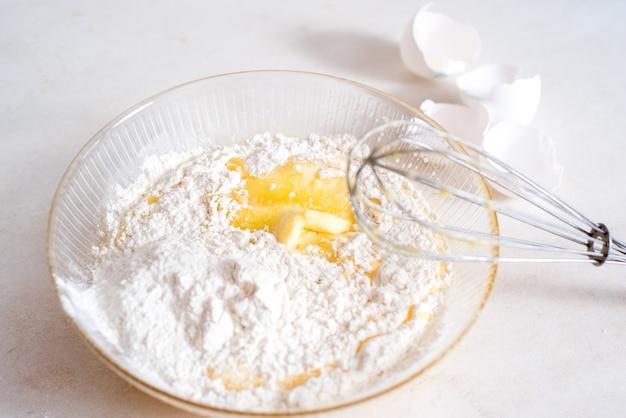 生地の作り方レシピ内の食材の量の測定。生地の成分:小麦粉、卵、麺棒、泡立て器、牛乳、バター、クリーム。 Premium写真