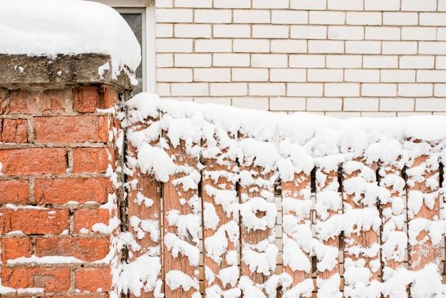 村の冬。木製の冷凍フェンス。雪とつららはどこにでもあります。 Premium写真