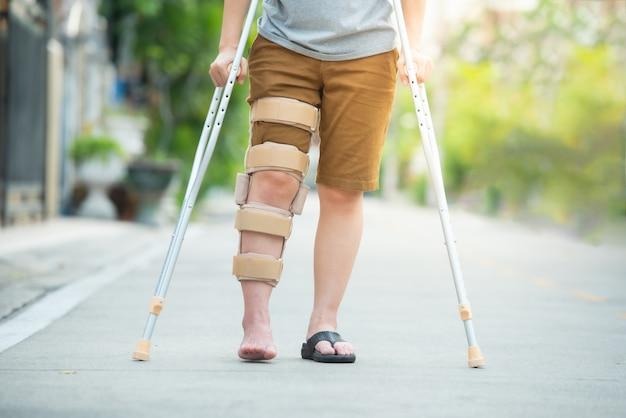 松葉杖や杖や膝サポートを持つ障害者の女性は、半身の後ろ側に立っています。 Premium写真