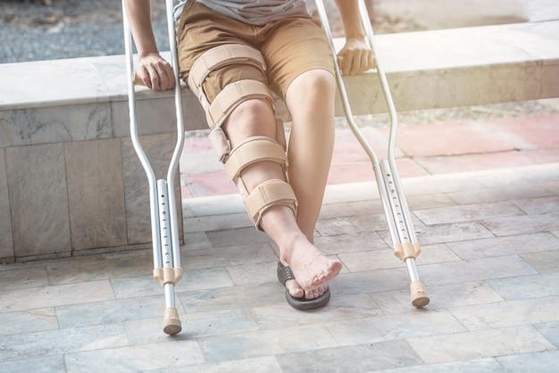 女性は杖とベンチに座って回復時間に膝ブレースサポート手術右膝。 Premium写真
