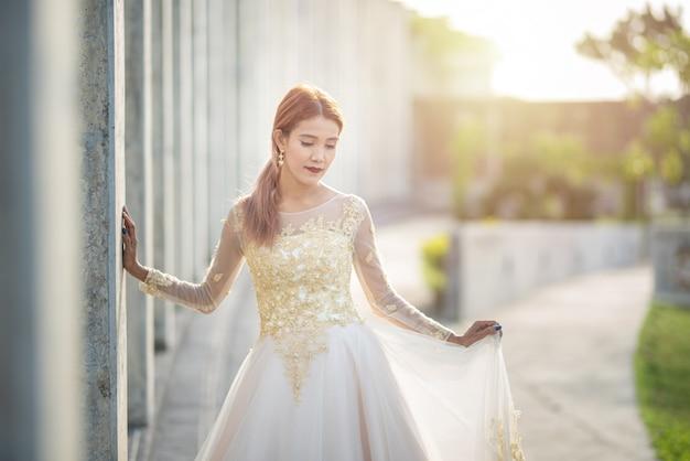 ウェディングドレスでアジアの花嫁の自然光と肖像画 Premium写真