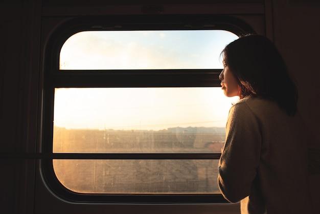 アジアの旅行者の女性は動いている電車の窓の外に見える Premium写真