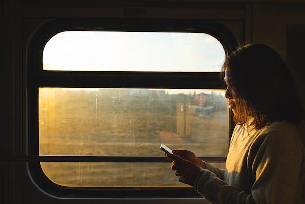 アジアの旅行者の女性は、動いている電車の窓の横にあるスマートな携帯電話を見てください。 Premium写真