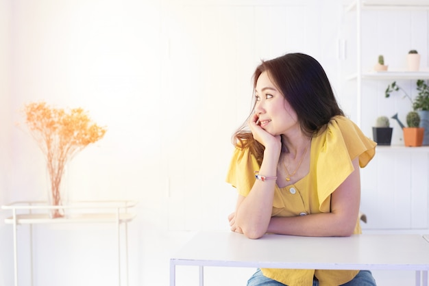 Портрет красивой азиатской женщины отдыхает ее голень на одной руке с стороной улыбки и смотрит вне окно с космосом экземпляра. Premium Фотографии