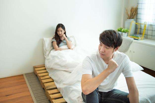 アジアの男性が落ち込んで、不幸な関係を持つ女性は、夫婦の生活の中で社会的な問題を議論した後、ベッドに座っています。 Premium写真
