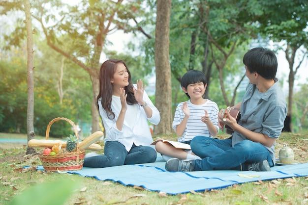 幸せなアジアの家族は公共の公園で余暇を持っています。父と母と息子はギターを弾く手を一緒に楽しんで、幸せな顔をしています。 Premium写真