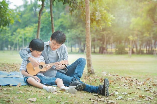 アジアの父は、公園でギターを弾く息子を教え、幸せな親子関係は屋外の庭でピクニック活動をしています。 Premium写真