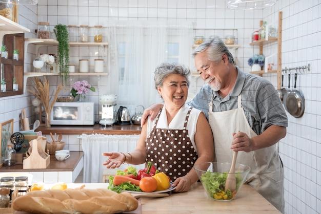 年配のカップルが健康食品とキッチンで楽しんで-引退した人が自宅で食事を調理する男と女のバイオ野菜とランチを準備-成熟した面白い年金受給者と幸せな高齢者の概念。 Premium写真