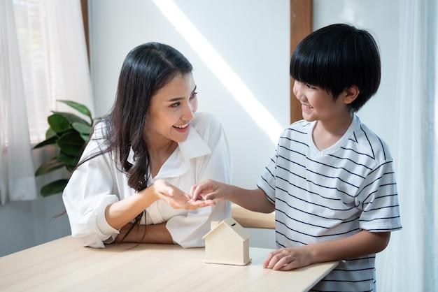 笑顔でボックスを保存する家のフォームで母の手にかわいいアジアの息子の手コイン Premium写真