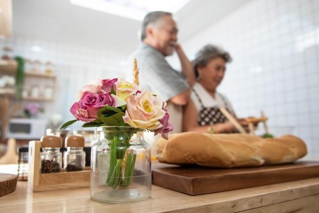 キッチンのテーブルの上のバラに焦点を当てたセレクティブディナーを調理する年配のシニアアジアカップル。愛はどこにでもあります。 Premium写真