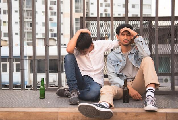 二人の男が酔って通りに一緒に座る Premium写真