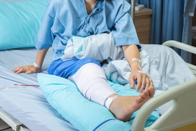 病棟病院のベッドで包帯圧縮膝ブレースで横になっているアジアの高齢者または高齢者の老婦人の患者。 Premium写真