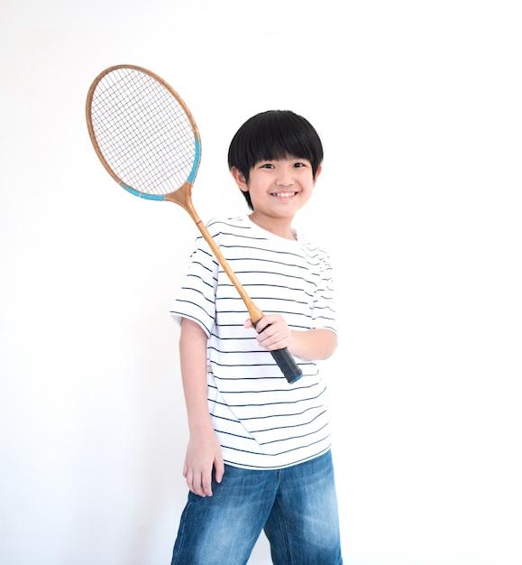 Маленький азиатский школьник с ракеткой на белой стене Premium Фотографии