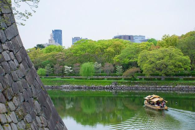 大阪城の堀に沿って観光客と観光客のボート Premium写真