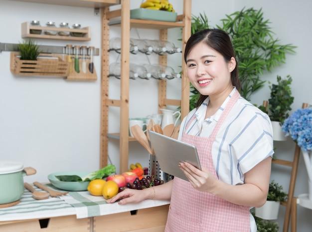 Счастливая азиатская женщина смотря рецепт кухни таблетки рецепта варя дома Premium Фотографии
