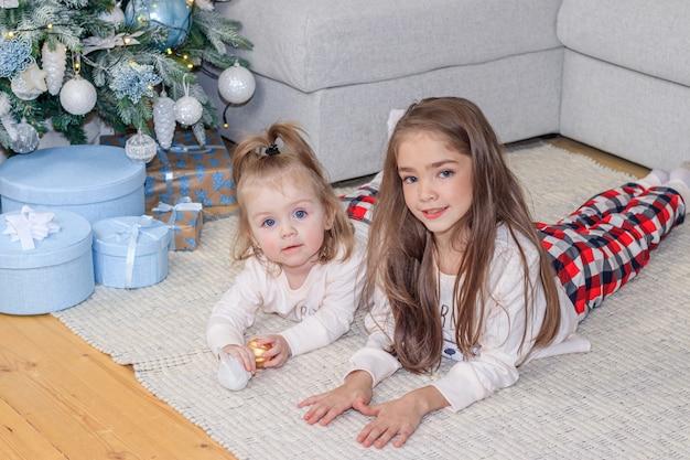 クリスマスツリーの近くの二人の姉妹。かわいい女の子。家の快適さ。クリスマスの飾り。 Premium写真