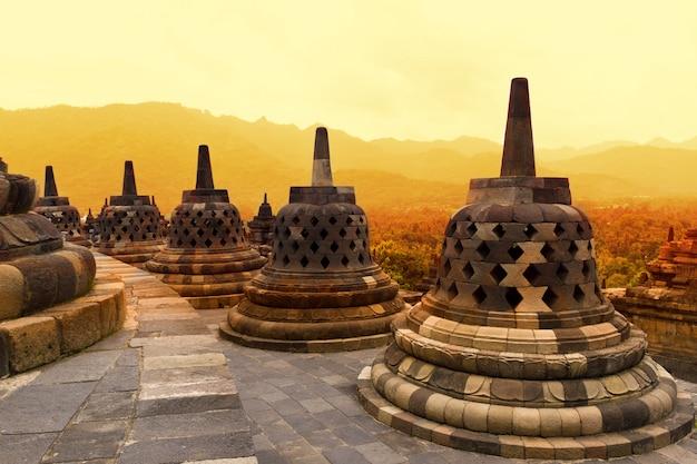 夕暮れ時のボロブドゥール寺院。ボロブドゥール寺院の古代の仏塔。 Premium写真