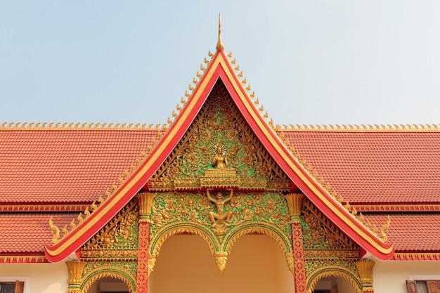 ラオスのビエンチャンで華やかな黄金の装飾が施された仏教寺院の赤い屋根の断片 Premium写真