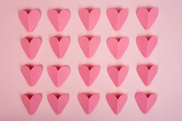 ピンクの背景のピンクの紙のハートの平面図です。行に配置された抽象的な紙のハート Premium写真