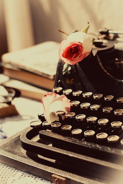 ピンクのバラとヴィンテージのタイプライター、テーブルの上の古い本。 Premium写真