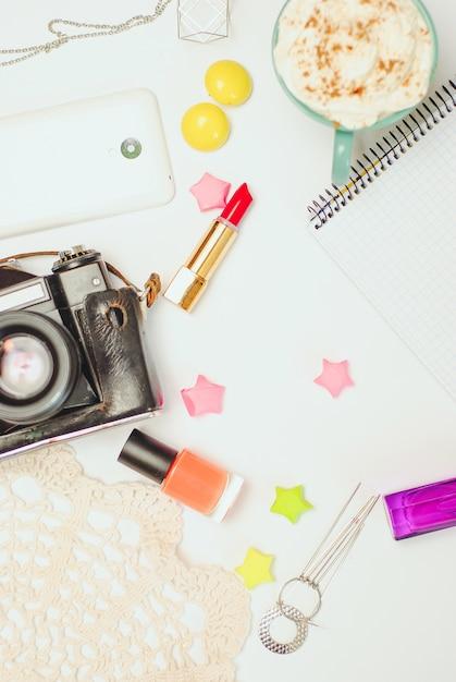 スマートフォン、ビンテージカメラ、コーヒー、化粧品の白い事務机テーブル。 Premium写真