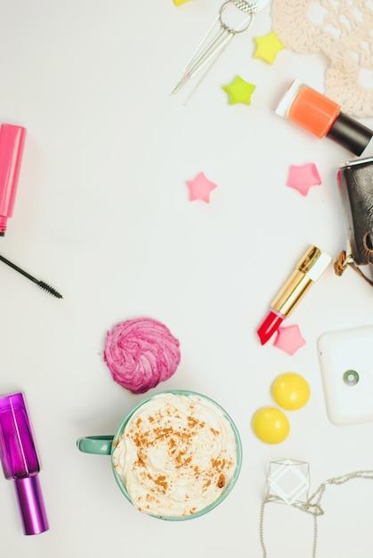 スマートフォン、ビンテージカメラ、スパイスラテ、化粧品の白い事務机テーブル。 Premium写真
