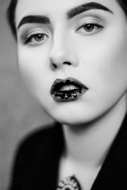 黒と白の写真をクローズアップで黒い液体の唇の創造的なメイクアップ。 Premium写真