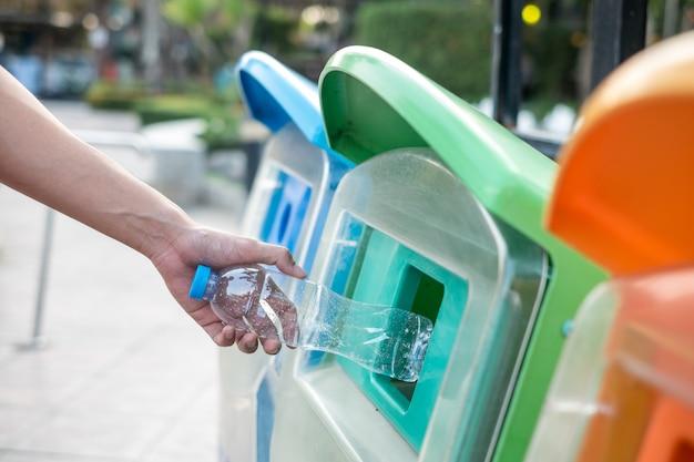男の手を保持しているとゴミ箱にペットボトルの廃棄物を入れます。 Premium写真