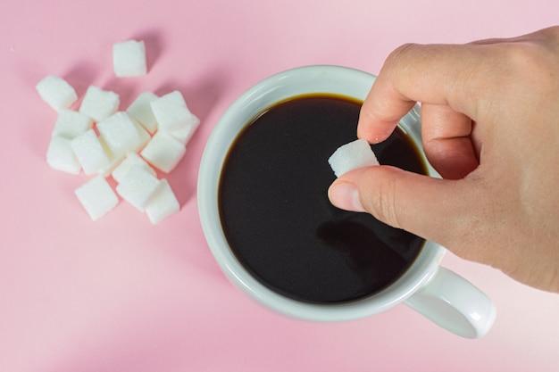 手はピンクのコーヒーで砂糖の立方体を満たしています。 Premium写真