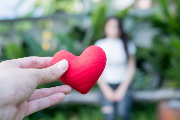 バレンタインの愛を置き換えるために、手は夕方に赤いハートを持っています。 Premium写真