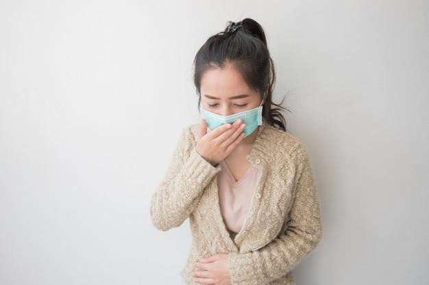 アジアの女性は細菌やほこりを防ぐために健康マスクを着用しています。健康管理についての考え Premium写真