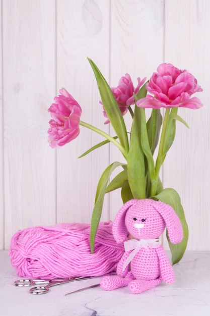 チューリップとピンクのウサギ。聖バレンタインデーの装飾。ニットおもちゃ、あみぐるみ、グリーティングカード。 Premium写真
