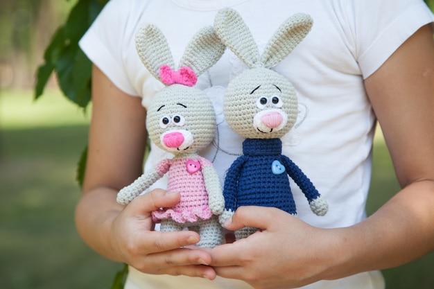 ニットのおもちゃを保持している公園の小さな女の子。手作り、あみぐるみ Premium写真