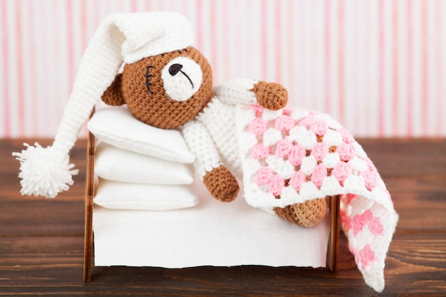 パジャマと寝袋で小さなニットテディベアは枕と眠っています。あみぐるみ。手作り。暗い背景の木 Premium写真