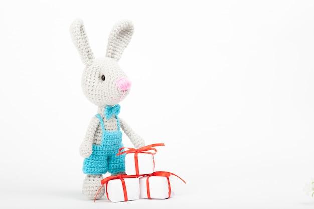 心を持つニットウサギ。聖バレンタインデーの装飾。ニットおもちゃ、あみぐるみ、グリーティングカード。 Premium写真