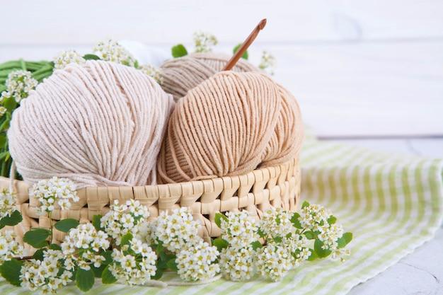 テーブルの枝編み細工品バスケットの糸のマルチカラーのもつれ。和風わびさび。家の快適さ、手芸。 Premium写真