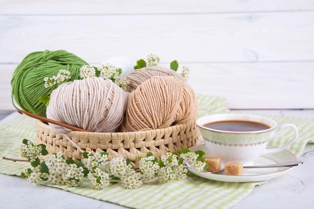テーブルの枝編み細工品バスケットの糸のマルチカラーのもつれ。美しい白いカップのお茶。和風わびさび。家の快適さ、手芸。 Premium写真