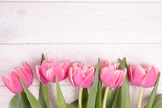 Нежные розовые тюльпаны на белом фоне деревянные. крупный план. композиция цветов. цветочный весенний фон. день святого валентина, пасха, день матери. Premium Фотографии