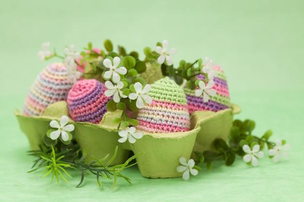 Вязаные пасхальные яйца декор, цветы на зеленом фоне, ручная работа Premium Фотографии