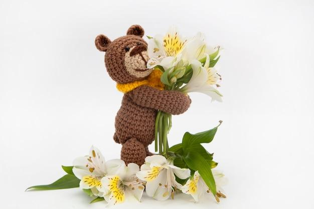 白い花、ニットのおもちゃ、手作りの小さなヒグマ。あみぐるみ。 Premium写真