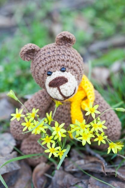 黄色いスカーフと小さなヒグマ。手作りニットおもちゃ Premium写真