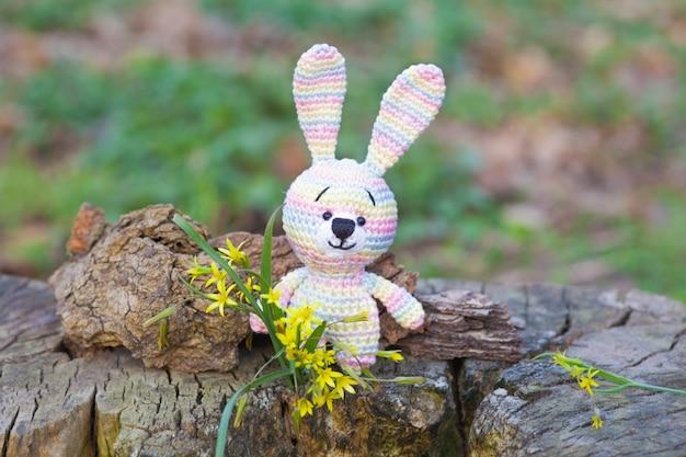 黄色い花を持つ小さなウサギ。手作りニットおもちゃ Premium写真