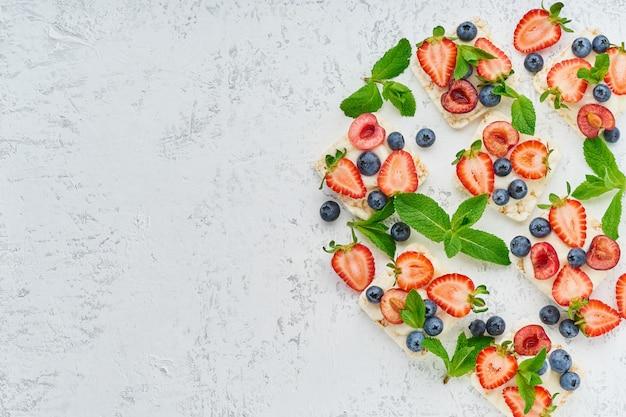 パステル調の背景コピースペース平面図に果実とフルーツのカラフルなコンセプトを持つクリスプブレッドを上昇します。 Premium写真