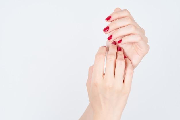 白地に赤いマニキュアでマニキュアの手を示す女性 Premium写真