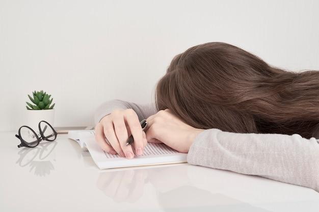 本とテーブルで寝て疲れている若い女性 Premium写真