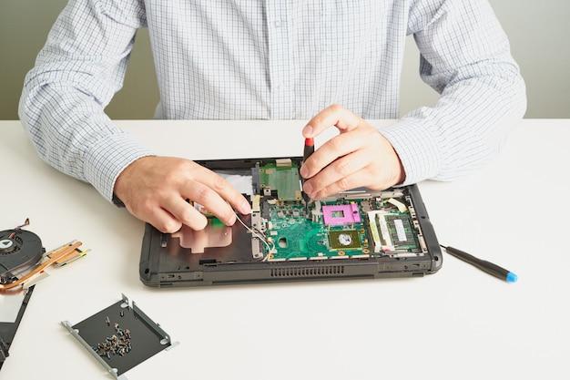 男はコンピューターを修理します。シャツのサービスエンジニアは、白い壁に白いデスクでラップトップを修理します。 Premium写真