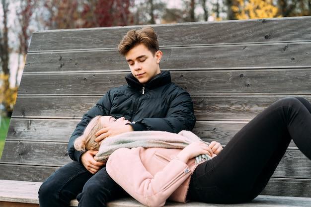 Влюбленные подростки сидят на скамейке в парке осенью, весело ...