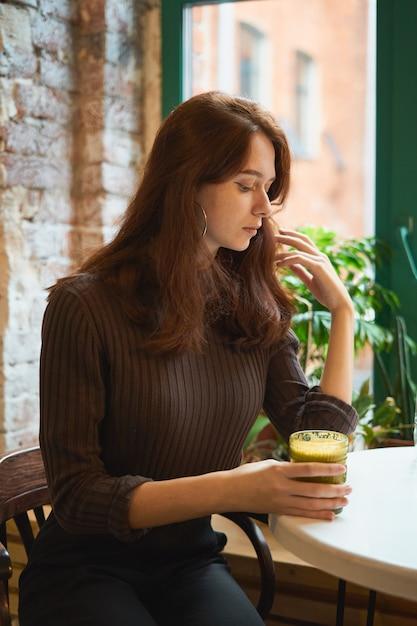カフェで窓際に座っている美しい深刻なスタイリッシュなおしゃれなスマートな女の子と健康的な黄色のスムージーを飲む Premium写真