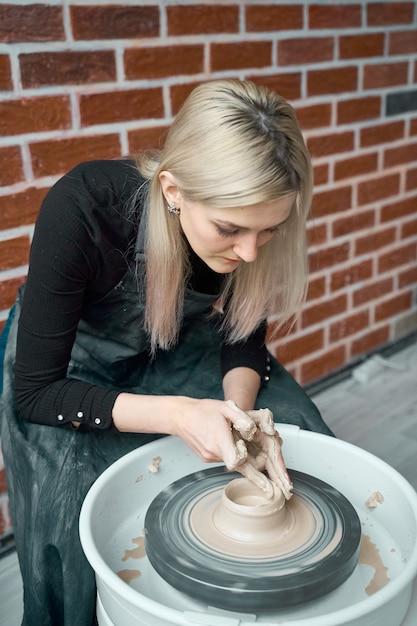 ホイール、手のクローズアップで陶器を作る女性。フリーランス、ビジネス、趣味の女性のためのコンセプト Premium写真